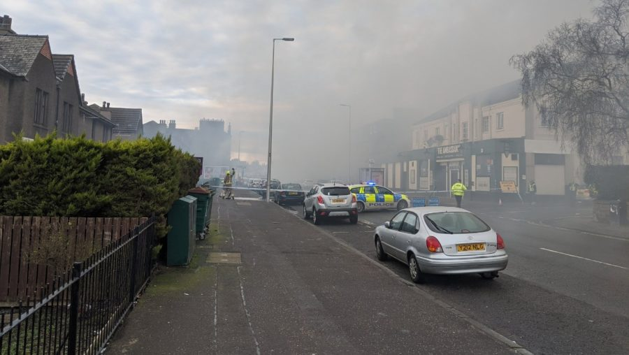 Fire: Blaze spreads to row of shops.