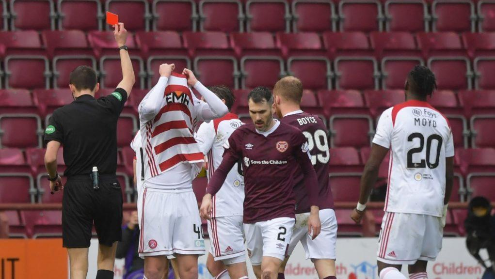 Jamie Hamilton hides his face after being shown the red card.