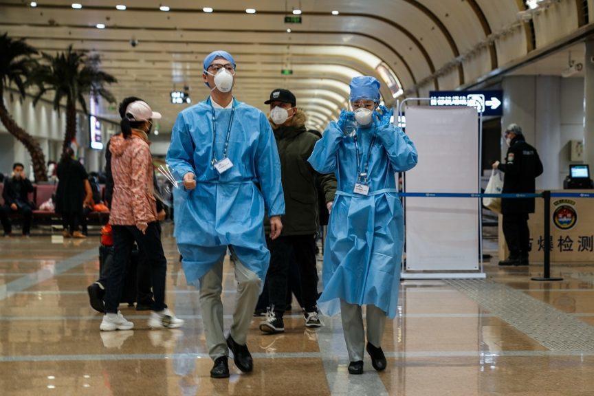 Coronavirus: Workers in protective gear at airport in Beijing.