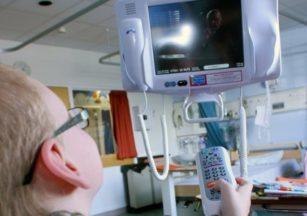 Patient with bedside hospedia television TV set.
