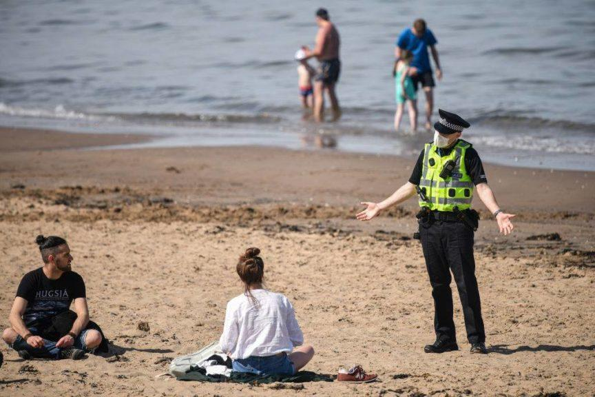 Officer remonstrating with people at Portobello Beach.