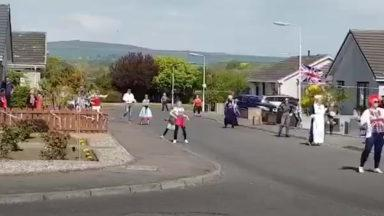 Young girl leads dance lessons on her street.