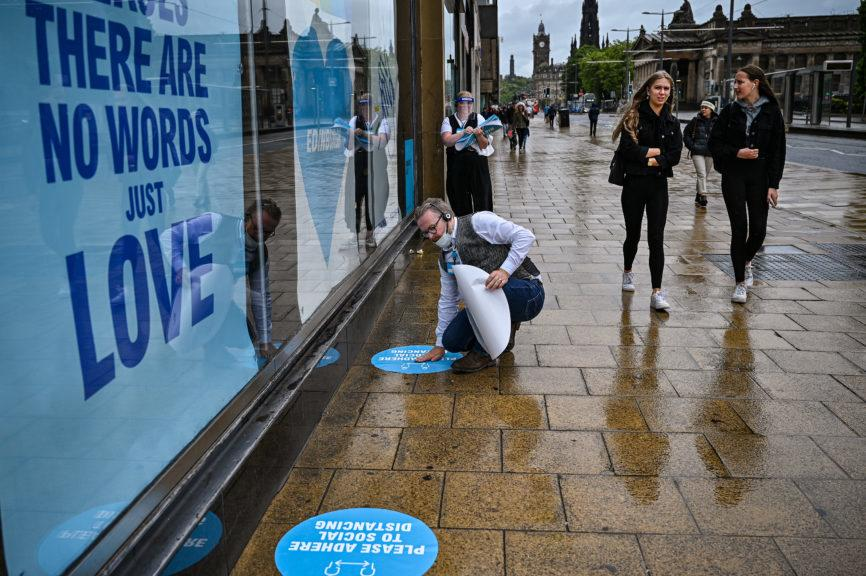 Shopping: Staff lay down social distancing markers at store in Edinburgh.