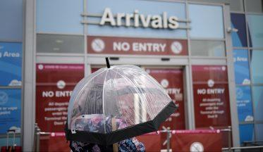 A woman waits for passenger arrivals at Birmingham Airport on July 27, 2020 in Birmingham, England. On Sunday the British government, concerned by a spike in coronavirus cases in Spain, reimposed a requirement for travelers returning from that country to self-isolate for 14 days. (Photo by Christopher Furlong/Getty Images)