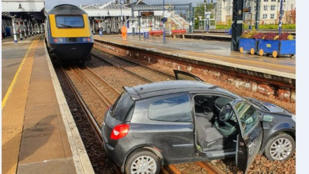 Car: Vehicle discovered lying across the tracks at train station.