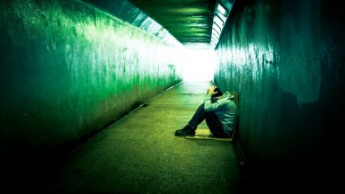 Homeless Depressed Man Sitting in Cold Subway Tunnel