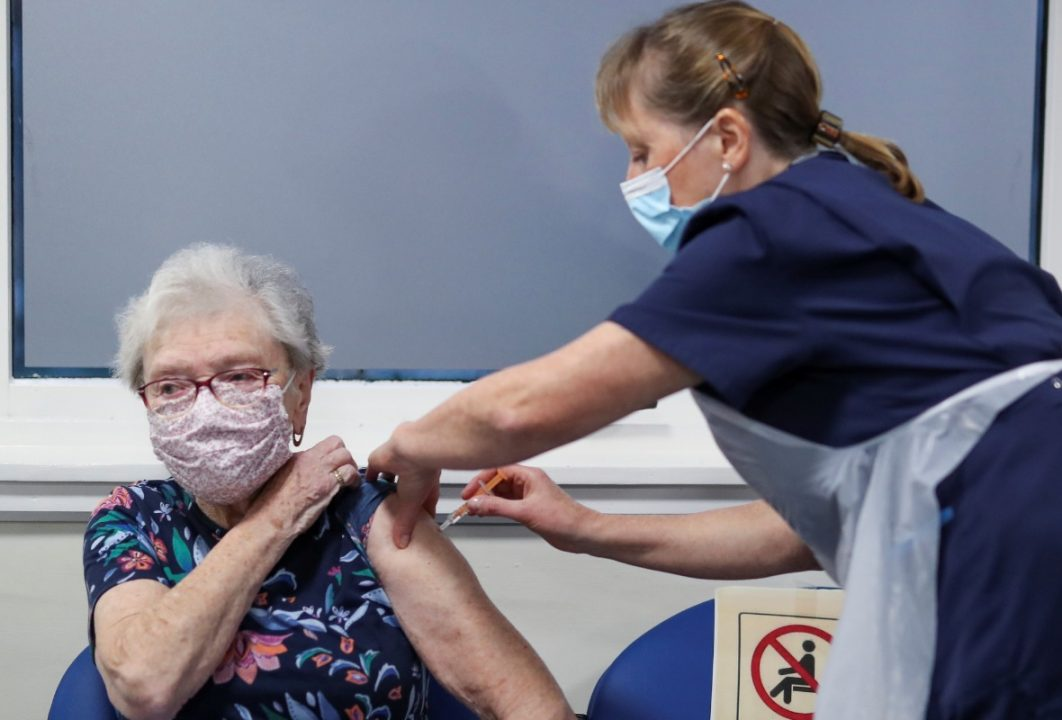 Lucy Airs receives a dose of AstraZeneca coronavirus disease (COVID-19) vaccine from Ruth Davies, a practice nurse, at the Pentland Medical Practice on January 7, 2021 in Currie, Scotland. The UK aims to vaccinate all over-70s, front-line health workers, and the most clinically vulnerable by mid February, when its current lockdown rules will be reviewed. That would require around 13 million covid-19 vaccinations.