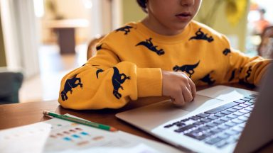 young boy studying and doing homework using his laptop