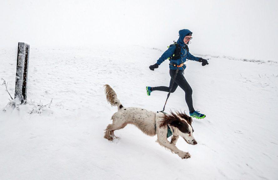 A woman runs with a dog through snow near Buxton in Derbyshire (PA)