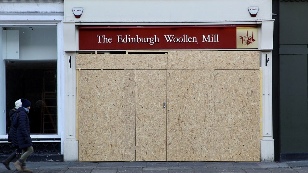 Boarded up branch of high street retail chain Edinburgh Woollen Mill on Princes Street.