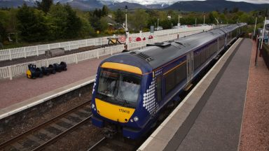 Aviemore, Scotland - June 2, 2015: ScotRail Class 170 Train at Aviemore Station Scotland in the distance snow on the hills.
