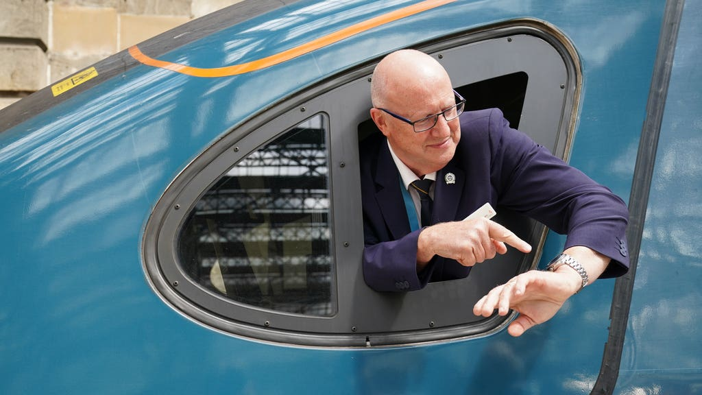 Driver Neil Barker looks at his watch after the train's arrival at Glasgow Central.