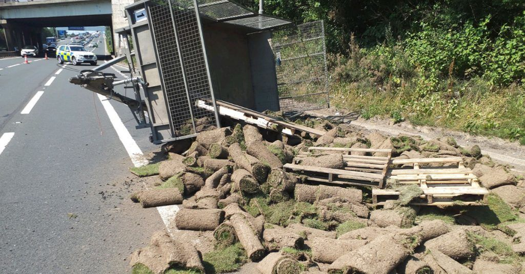 Trailer full of turf overturned strewing debris across the road near Junction 27, on the M8 in Glasgow.