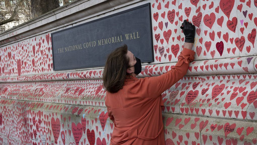 Woman writing message on Covid memorial wall in London.