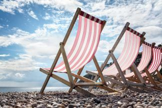 Deck chairs on the beach at the seaside on summer vacation