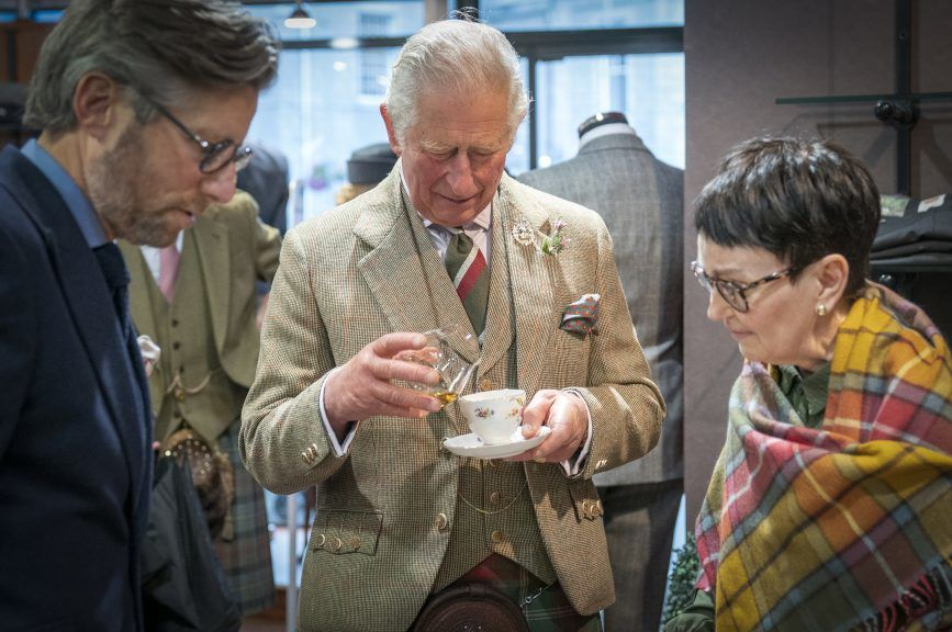 Mixed drinks: Charles enjoys cuppa with a dash of whisky at kilt shop.